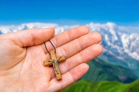 Female hand with wooden cross on mountains background - religion concept