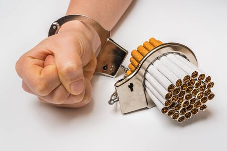 lock symbol: Female hand with handcuffs and cigarettes on white background - concept of smoking dependence