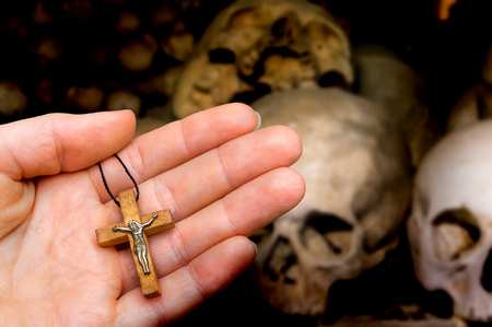 Female hand with wooden cross on skulls and bones background - religion concept Stock Photo