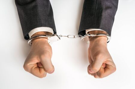 Male hands in handcuffs isolated on white background