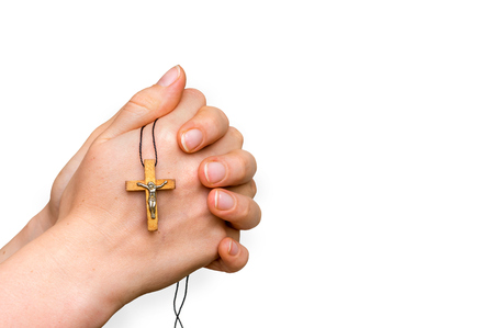 Woman hands holding wooden cross isolated on white background - religion concept