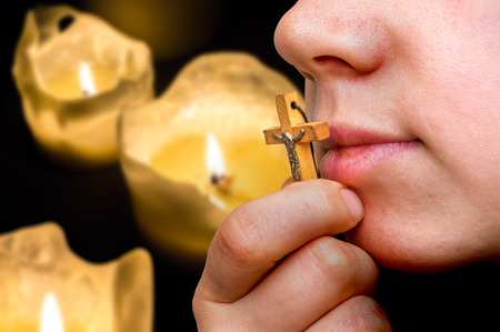 Female hand with wooden cross on burning candles background - religion concept