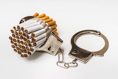lock symbol: Cigarettes and handcuffs - smoking addiction concept on white background