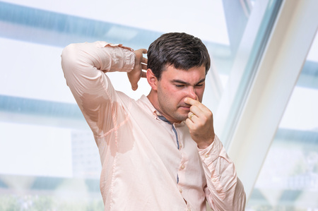 Business man with sweating under armpit pinches nose with fingers in office