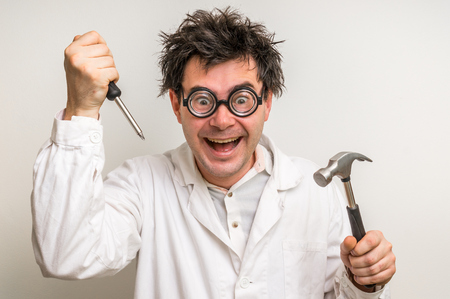 Crazy scientist repairing something with hammer and screwdriver Stockfoto