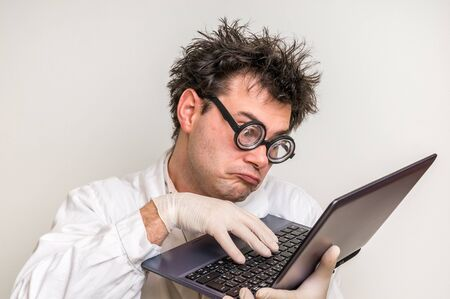Crazy scientist in glasses with laptop working in his laboratory