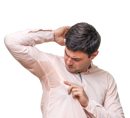Young man with sweating under armpit in pink shirt isolated on white