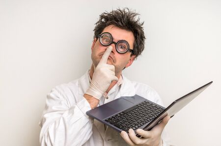 messed: Crazy scientist in glasses with laptop working in his laboratory