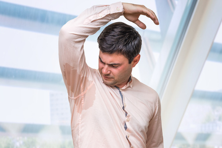 Man with hyperhidrosis sweating under armpit in pink shirt