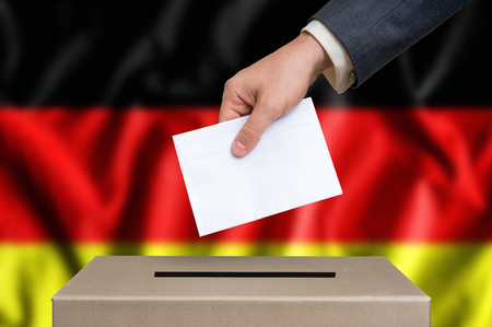 Election in Germany. The hand of man putting his vote in the ballot box. German flag on background.