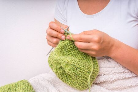 Female hands with needles knitting with green wool at home