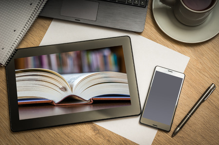 bookish: Digital tablet on business table with open book in library on screen and mobile phone, paper, pen, laptop and cup of coffee - above view Stock Photo