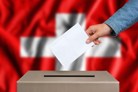 Election in Switzerland. The hand of woman putting her vote in the ballot box. Swiss flag on background. Stock Photo