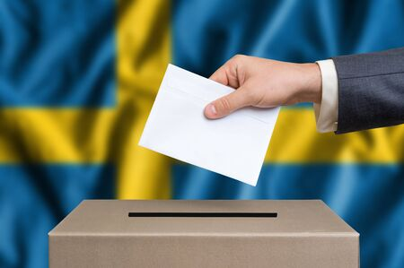 Election in Sweden. The hand of man putting his vote in the ballot box. Swedish flag on background. Stock Photo