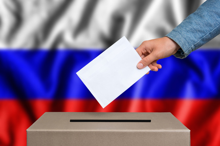 Election in Russia. The hand of woman putting her vote in the ballot box. Russian flag on background.