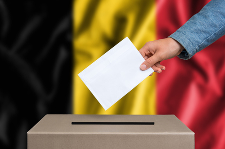 Election in Belgium. The hand of woman putting her vote in the ballot box. Belgian flag on background.