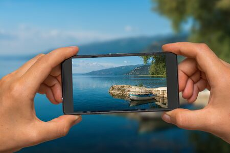 Woman hands with mobile cell phone to take a photo of Ohrid lake in Macedonia Stock Photo