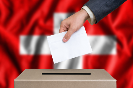 Election in Switzerland. The hand of man putting his vote in the ballot box. Swiss flag on background. Stock Photo