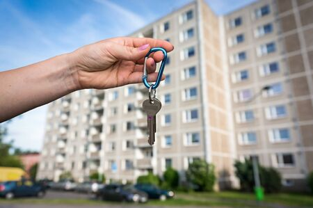 Real estate agent giving flat keys to a new property owner on blurred background