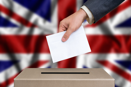 Election in United Kingdom. The hand of man putting his vote in the ballot box. United Kingdom flag on background. Stock Photo