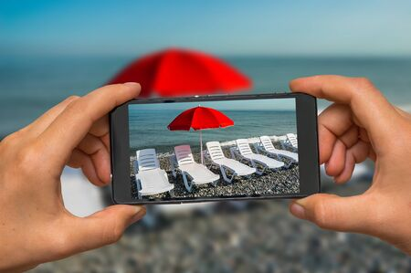 Woman hands with mobile cell phone to take a photo of sunbathing plastic beds and red umbrella on the beach