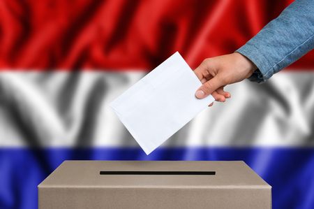 Election in Netherlands. The hand of woman putting her vote in the ballot box. Dutch flag on background. Stockfoto