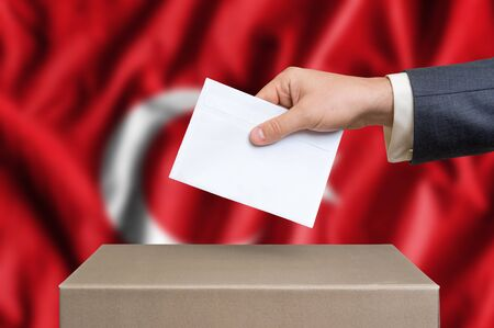 Election in Turkey. The hand of man putting his vote in the ballot box. Turkish flag on background.