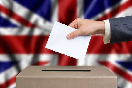 Election in Great Britain. The hand of man putting his vote in the ballot box. British flag on background. Stock Photo