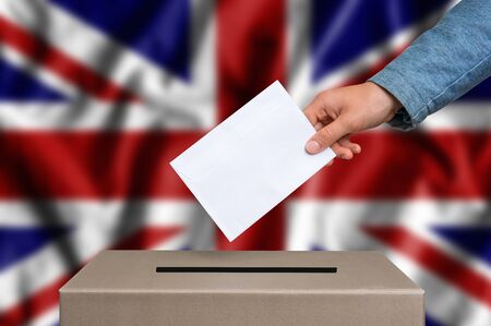 Election in Great Britain. The hand of woman putting her vote in the ballot box. British flag on background. Stock Photo