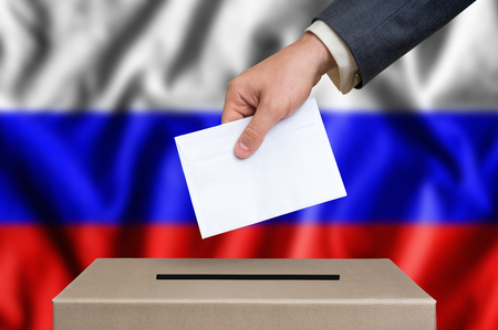 Election in Russia. The hand of man putting his vote in the ballot box. Russian flag on background.