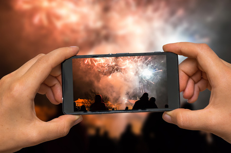 Woman hands with mobile cell phone to take a photo of fireworks