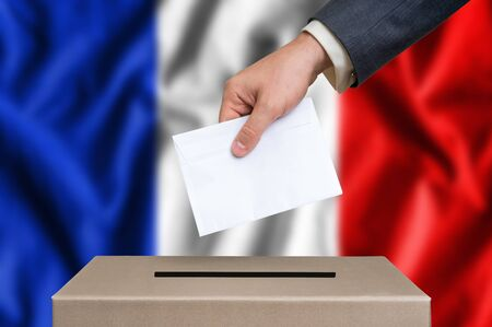 Election in France. The hand of man putting his vote in the ballot box. French flag on background. Stock Photo