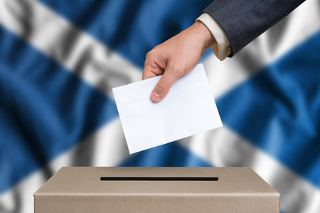 scottish parliament: Election in Scotland. The hand of man putting his vote in the ballot box. Scottish flag on background. Stock Photo