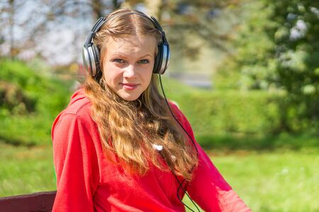 earpiece: Young lady listening to music and relaxing on a park bench