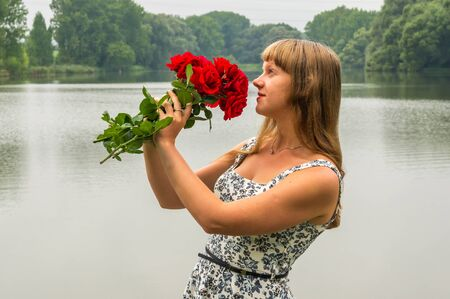 Beautiful young lady by the lake holds a roses Stock Photo