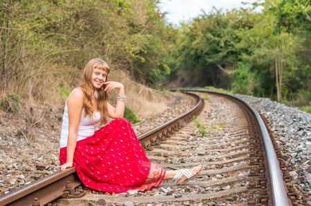 Young lady in red dress sitting on railway tracks Stock Photo