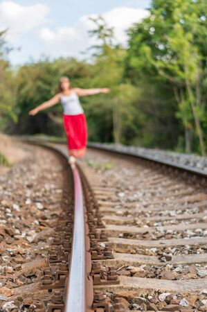 Young lady in red dress walking on railway tracks