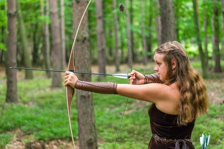 Young lady Elf with a long bow in the wild forest Stock Photo
