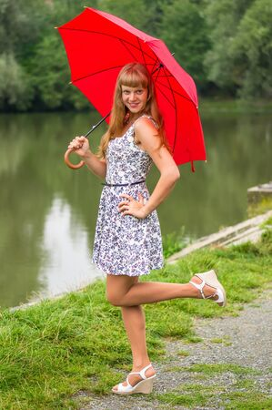 Beautiful young lady with red umbrella near the pond