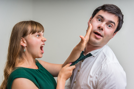 Angry woman in green dress giving a slap in the face to her husband in home - domestic violence concept