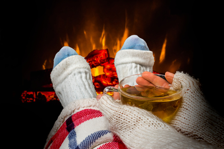 Woman resting with cup of tea near fireplace at home