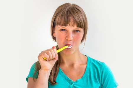 Young lady brushing teeth in the morning - dental hygiene Stock Photo