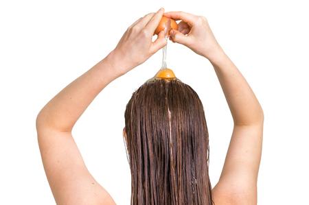 魅力的な女性は白い背景に分離されて - 彼女の髪に卵コンディショナーを適用します。