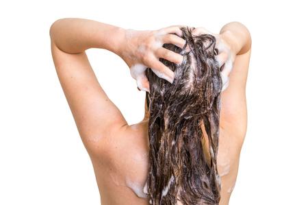 Het aantrekkelijke haar van de vrouwenwas met shampoo in douche - die op witte achtergrond wordt geïsoleerd