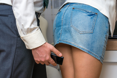 obscenity: Man taking photo with mobile phone of womans butt - sexual harassment in business office
