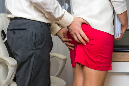 Man touching woman's butt - sexual harassment in business office Stockfoto