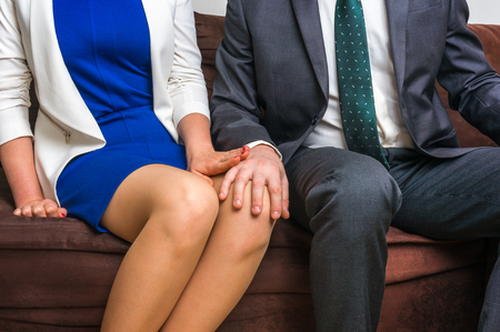 Man touching woman's knee - sexual harassment in business office 스톡 콘텐츠