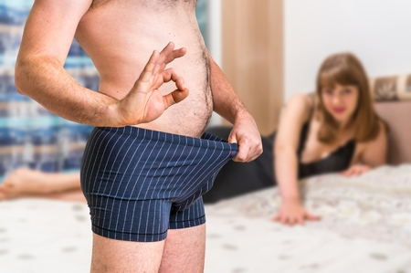 Attractive woman in bed and man in underwear is looking inside and is showing OK gesture - impotence concept