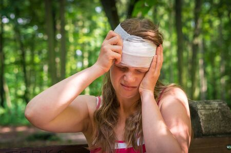 Woman applying compression bandage on her head after injury in nature Stock Photo