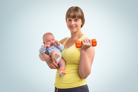 Happy young lady strengthens with dumbbell after childbirth and holds newborn baby